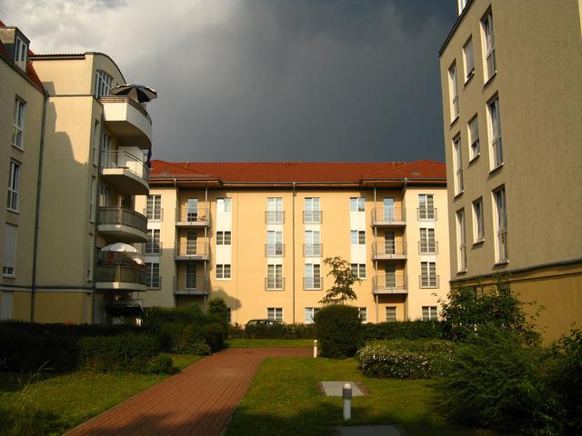 panelové domy, tvořící U, naproti s červenou střechou, dokola je tráva a hezká zeleň, s fasádami do žluta