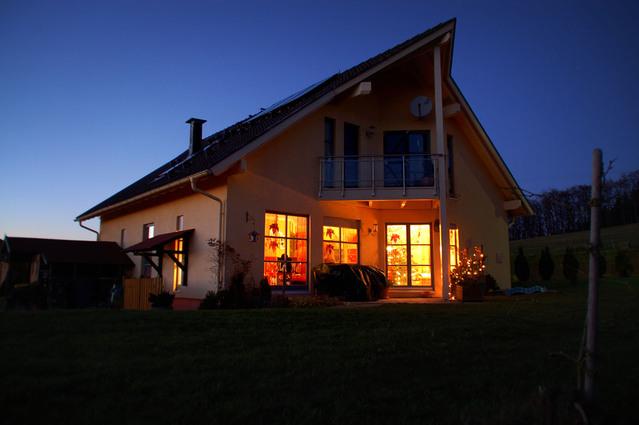 novostavba s oranžovou fasádou, je přítmí a svítí v domečku okna ve spodním patře