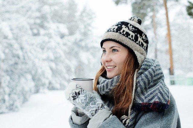 žena v zimě venku, drží plecháček má čepici a rukavice a za ní je sníh