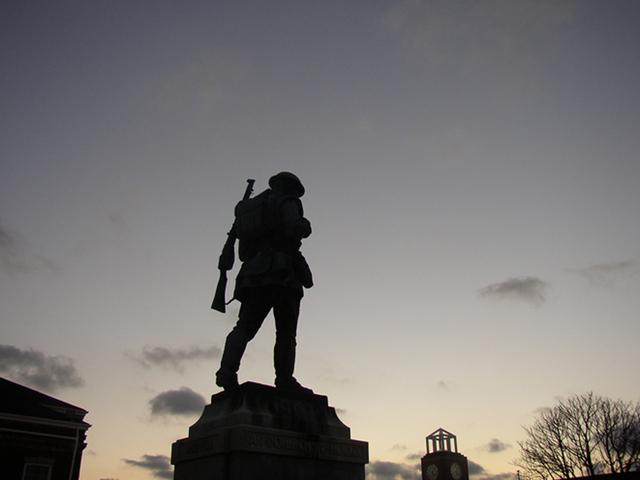 nadživotní socha vojáka v pochodu za západu slunce
